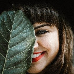 woman covering face with leaf