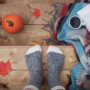 cozy picture of feet on wooden deck with leaves, blanket, coffee, a book and pumpkin